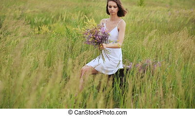 Beautiful young girl with flowers in summer field
