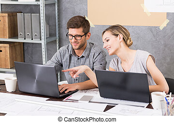This one is great - Man and woman sitting beside desk in...