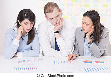 Racking brains on charts - Three co-workers analyzing the...