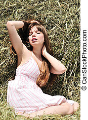 Woman lying in haystack - Woman lying in dry grass and...