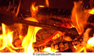 Stirring burning firewood at brick fireplace with a poker 4K...