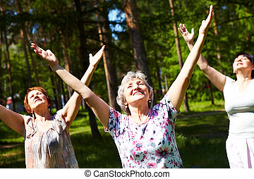 Energy - Portrait of aged women with their arms raised in...