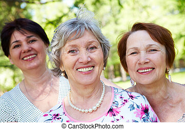 Female friends - Portrait of three aged women looking at...