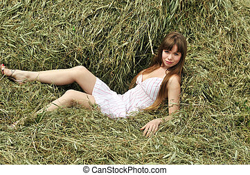 woman relaxing on the hayloft - sensual young woman relaxing...