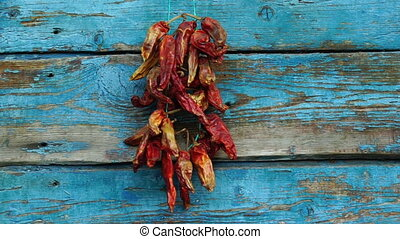 footage men hangs dried red pepper on a wooden wall slow...