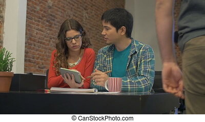 Asian Business man caucasian woman using tablet computer...