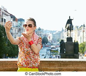 Happy young woman blowing air kiss and taking selfie in...
