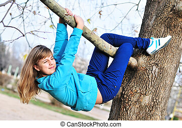 she is a sloth - Teen girl hanging on the tree in autumn...