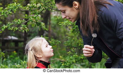 Mother and daughter blowing blowball - Happy mother and...