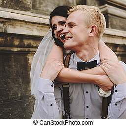 groom carries bride on his back, outdoors