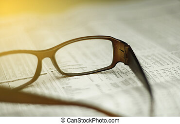 closeup of glasses on a newspaper with a very shallow depth...