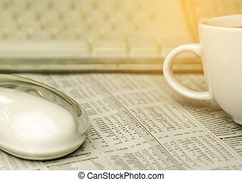 mouse , a cup of coffee and keyboard on a newspaper with burst light