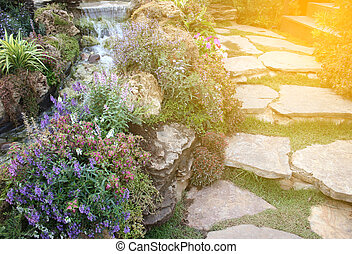 Walk way in beautiful garden with small waterfall with burst...