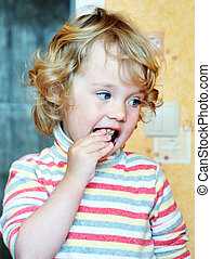 girl eating sweets - happy little girl eating sweets at the...
