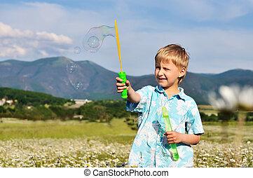 boy and soap bubbles - funny little boy blowing soap bubbles...