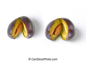 halved fresh plums - two halved ripe plums on white...