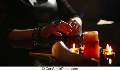 Witch - fortune teller with candles close up magic ritual...