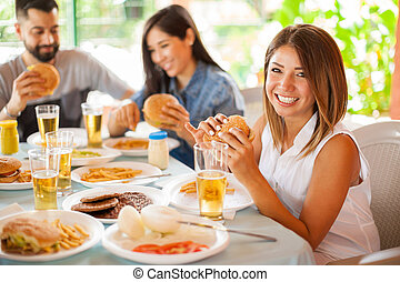 Cute brunette eating a burger with her friends