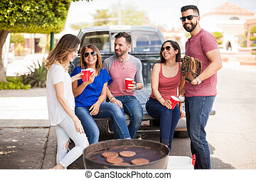 People tailgating at a baseball game - Group of young adults...