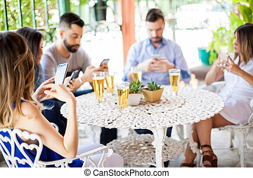 Using smartphones during a friend reunion - Five young...