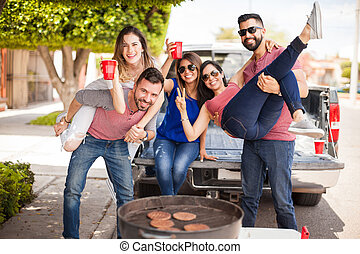 Group of people tailgating and grilling burgers - Group of...