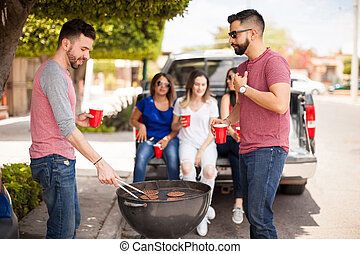 Male friends grilling hamburgers outdoors - Two handsome...