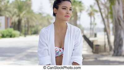 Calm woman in white robe sitting outdoors - Single young...