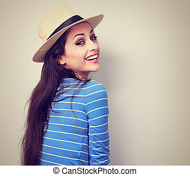 Beautiful long hair laughing woman in blue top and straw hat looking. Toned closeup portrait