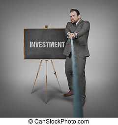 Investment text on blackboard with businessman pulling rope...