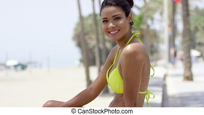 Cute woman in yellow bikini sitting on beach wall - Cute...