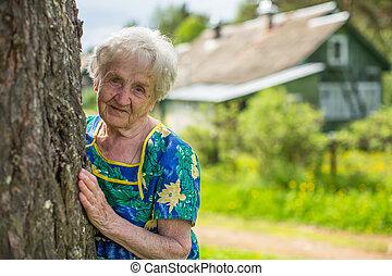 An elderly woman near his home