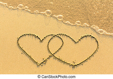 Couple of hearts drawn by hand on a sandy golden sea beach.