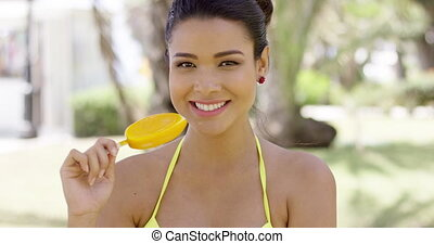 Happy woman eating icicle dessert - Single happy smiling...