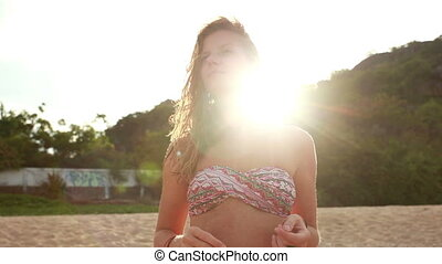 Woman smiling and looking in camera at sunset