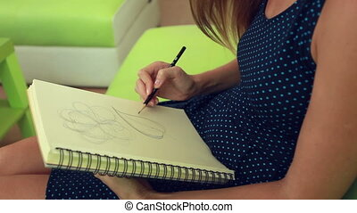 Woman drawing in album - Woman drawing floral elements in...