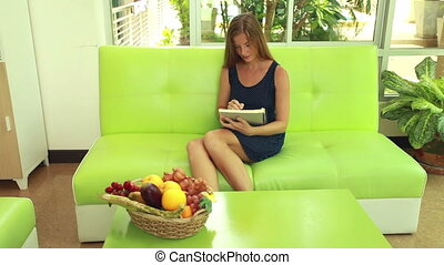 Beauty woman drawing in album - Woman sitting on green sofa...