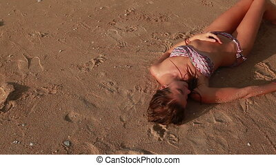 Woman lying on the beach - Woman lying down on the beach and...