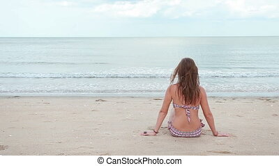 Woman sitting on the beach near the sea - Adult woman in...