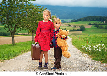 Two cute kids, little girl and her brother, walking down the...