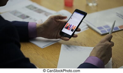 Man at meeting, holding a pen in hand and scans news with a smartphone.