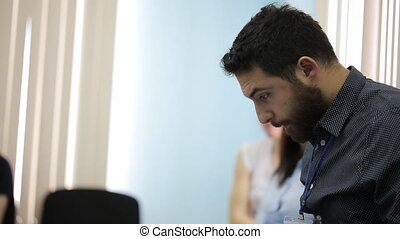 Man with beard in dark shirt is prepared for presentation at conference.