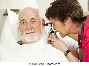 Home Health Nurse Checks Ears - Home health nurse checking...