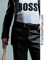 Cropped view of man with bat and boss on shirt - Cropped...