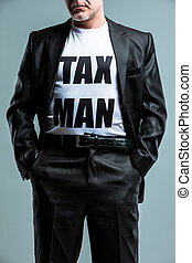 Stern man wearing a Tax Man t-shirt standing with his hands...