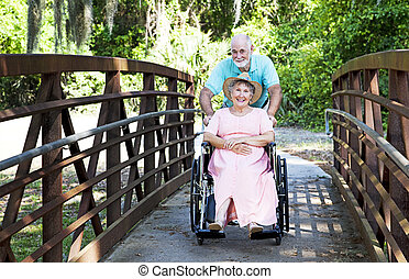 Senior Pushes Wife in Wheelchair - Senior man pushes his...