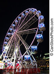 Ferris wheel at night - Amusement park attractions. Spinning...