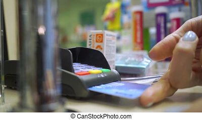 Girl paying with her credit card in a drugstore close up...