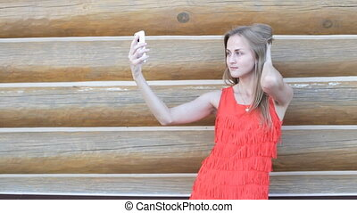 Woman taking self portrait outdoors. Beautiful young woman...