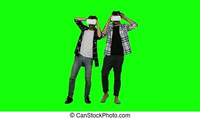 Young mans wearing virtual reality VR glasses. Green screen...