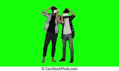 Two young man with a virtual reality headset. Green screen -...
